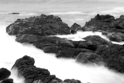 black ocean rocks in white mist, monochrome