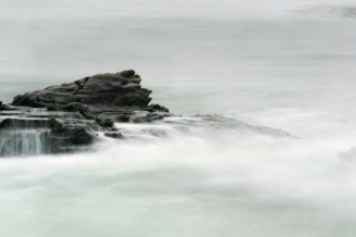 ocean rocks waves form waterfalls, white mist