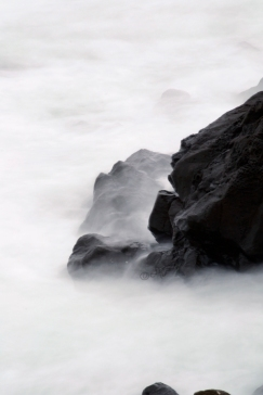 black ocean rocks, waves white mist