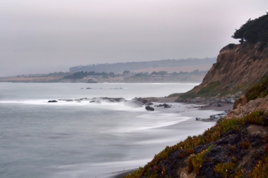 Misty dusk ocean waves cliffside shore