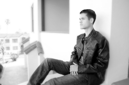 Pensive young man, high school senior. leather jacket and jeans