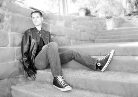 Pensive young man, high school senior. leather jacket and jeans, sitting on steps