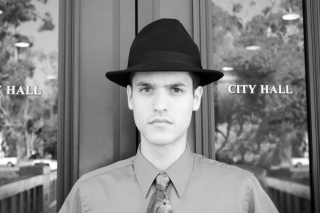 Serious young man, tie and detective hat, City Hall