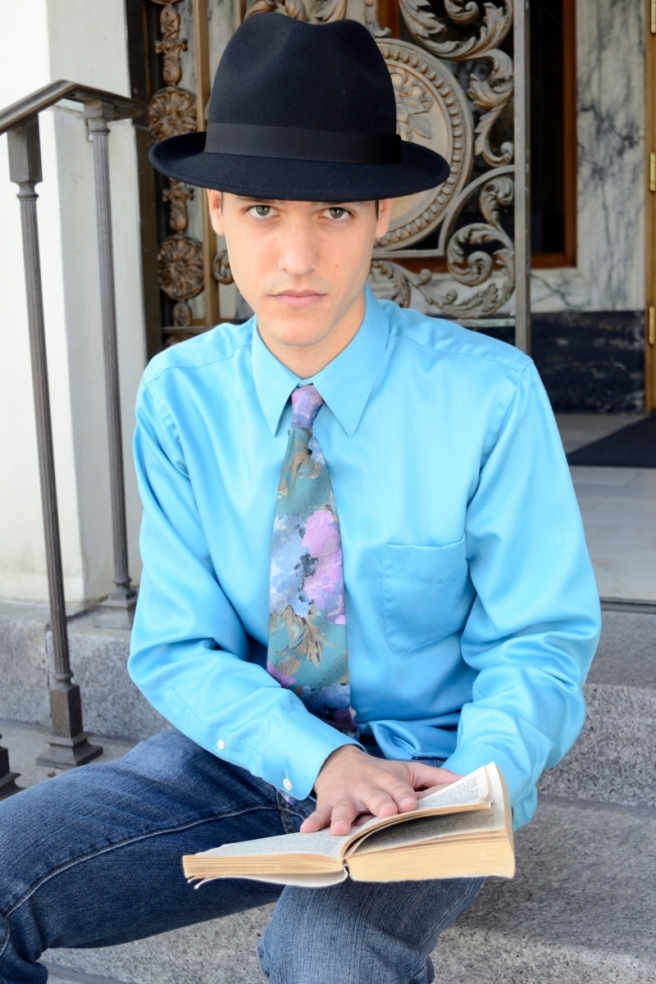 Young man, sitting at steps, hat and tie, reading
