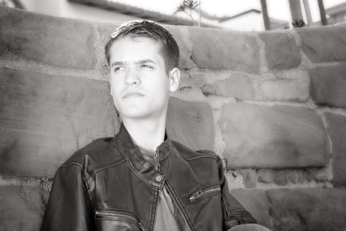 Pensive young man, high school senior. leather jacket
