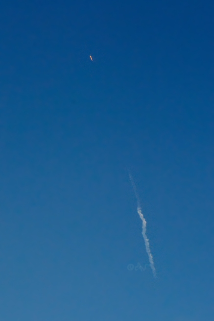 SpaceX Falcon midday rocket launch over hillside