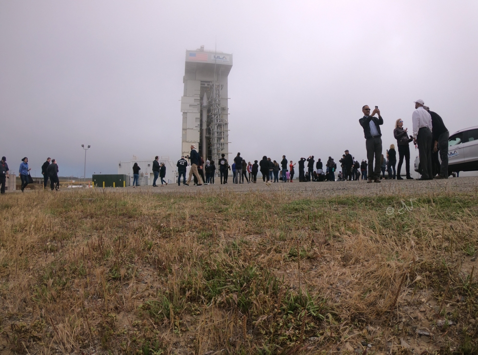 Erect rocket amidst fog, crowd photographing
