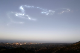 Delta ii rocket launch smoke plume - silver and pink, over city during dawn