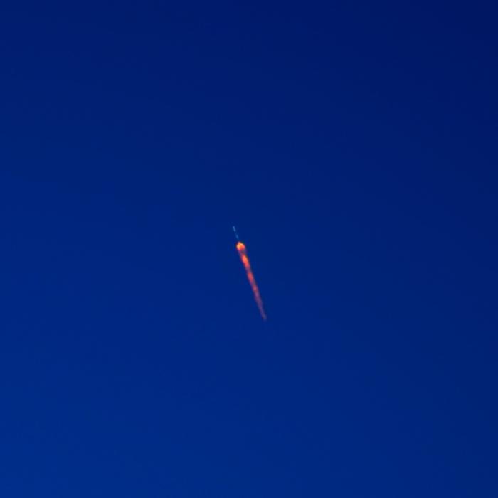 spiraling Falcon 9 rocket against blue sky