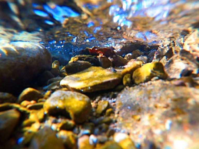 underwater in creek, rocks, pebbles and blue water ripples on surface