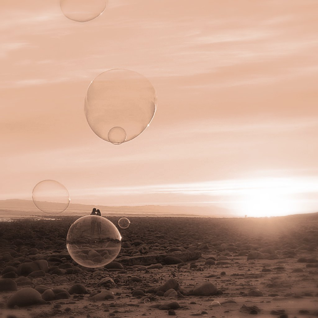 bubble in foreground floats just under a couple kissing on beach; sunset in background. Monochrome sepia.