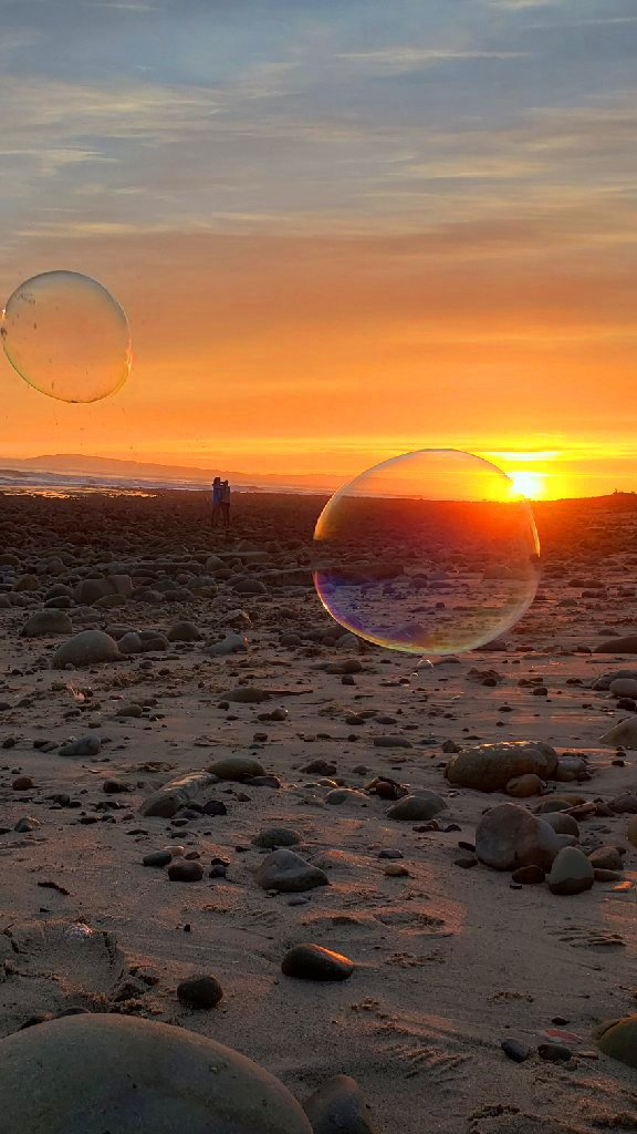 couple looks at sunset, two bubbles in foreground. Yellow orange sunset in background.