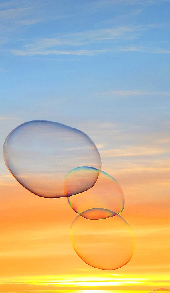 Abstract colorful bubble shape, blue and orange sunset in background