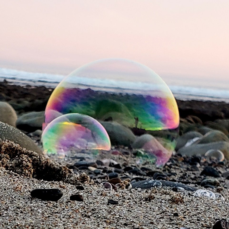 Big bubble linked to smaller bubble , both resting on sand and stones. Big bubble reflects silhouette of woman with bubble wand. Ocean in background. Pink sky.