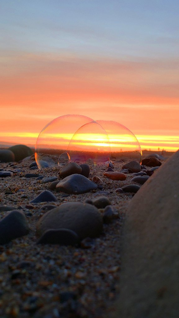 two bubbles linked together rest on stones on sand by a big rock; yellow and orange sunset in background