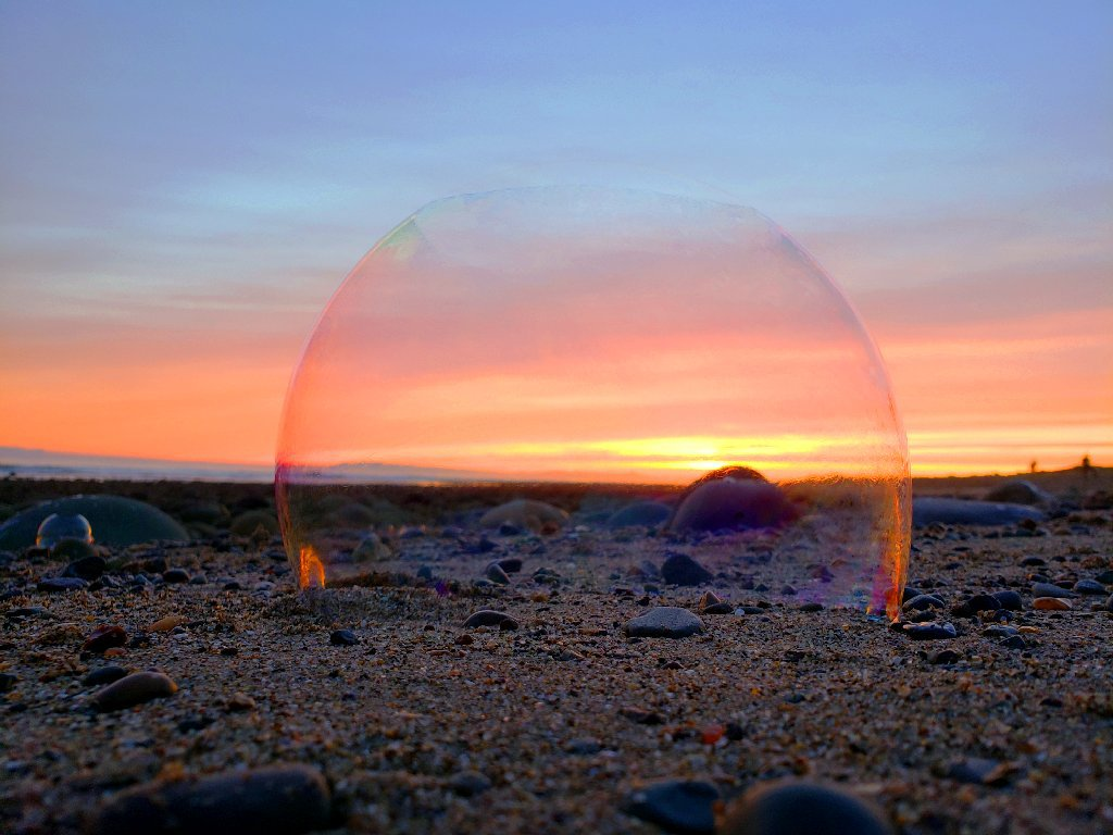fading bubble rests on sand and stones, yellow and pink sunset in background