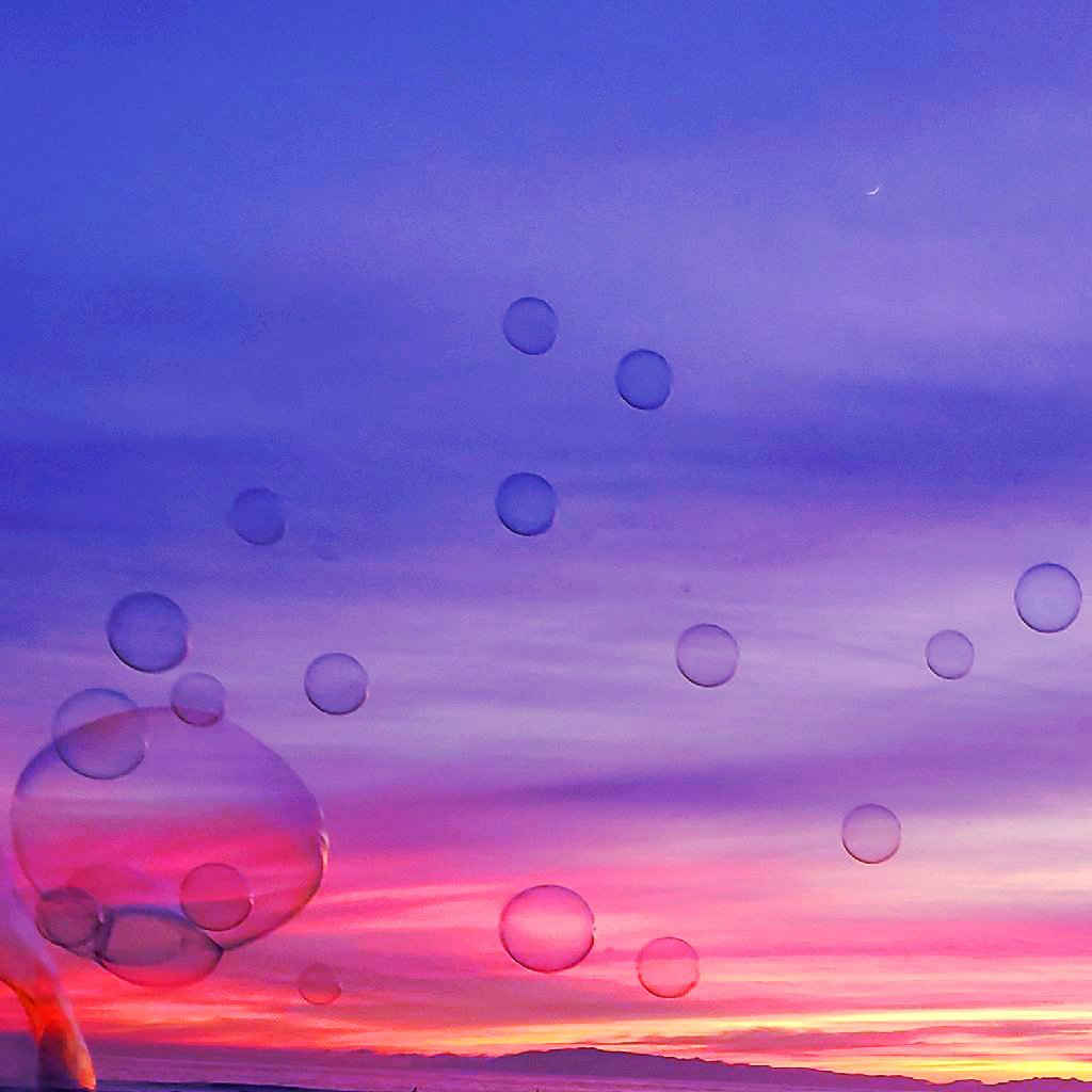 Many bubbles float up toward waxing crescent moon. Purple and magenta oversaturated sky.