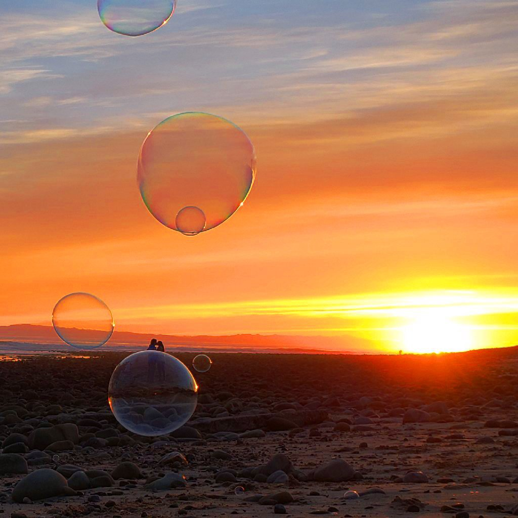 bubble in foreground floats just under a couple kissing on beach; orange sunset in background