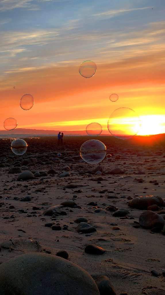 couple looks at sunset, bubbles around them in foreground.