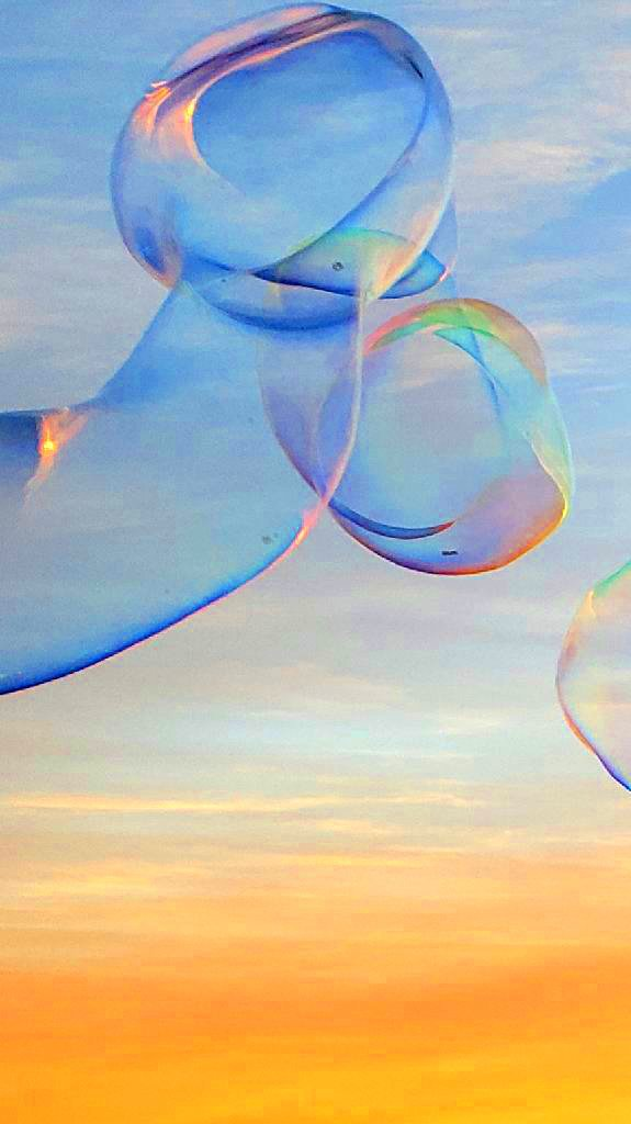 Abstract colorful bubble shape, blue and orange sky over ocean in background
