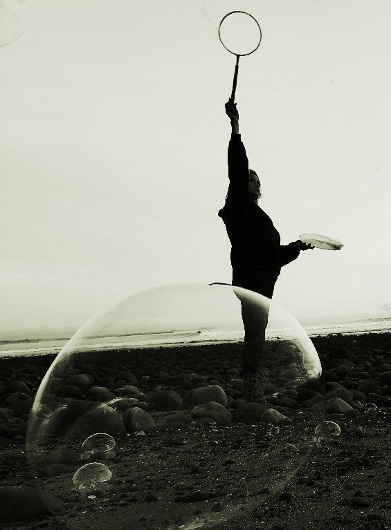 Woman stands before ocean, creates giant bubbles with wand; silhouette monochrome