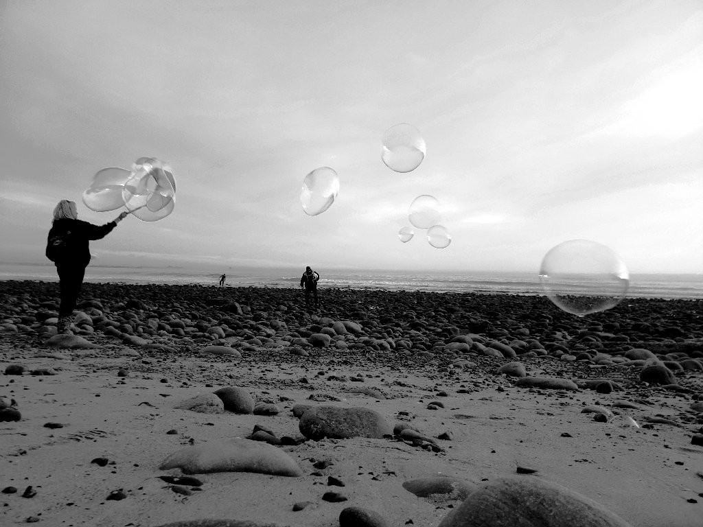 monochrome black and white, woman on sand making giant bubbles