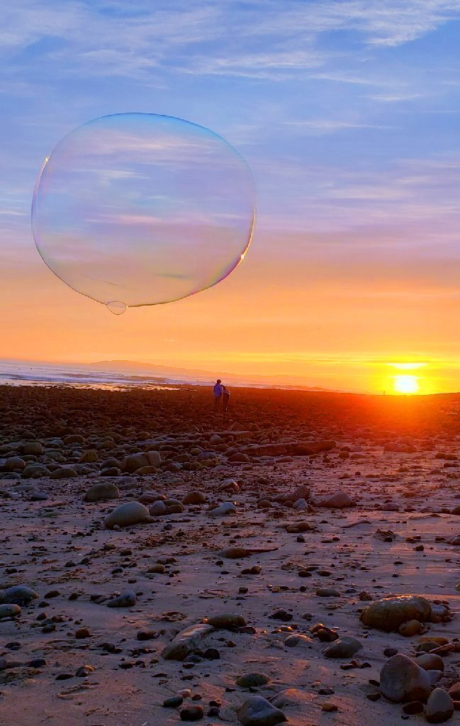 couple watches beach sunset; bubble hovers over them