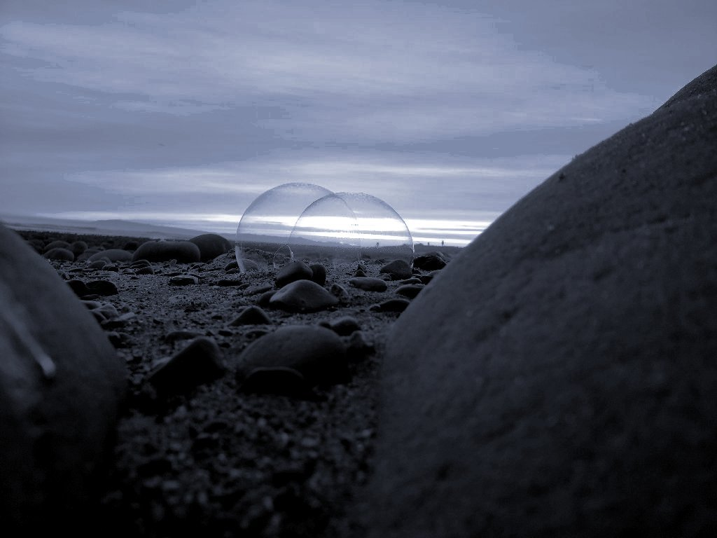 two bubbles linked together rest on stones on sand by a big rock; monochrome, blue tone