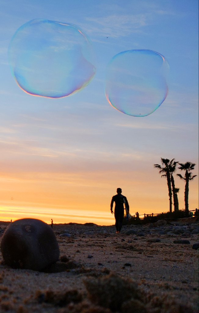 Surfer walks toward sunset; three palm trees to his right, two big bubbles float above him