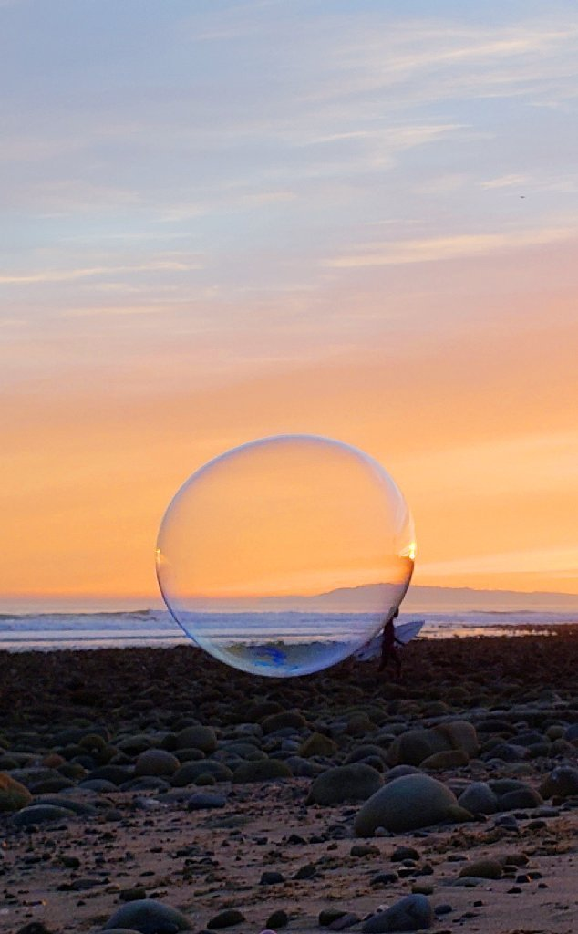 bubble in foreground appears to float attached behind background surfer's head; orange and blue sky