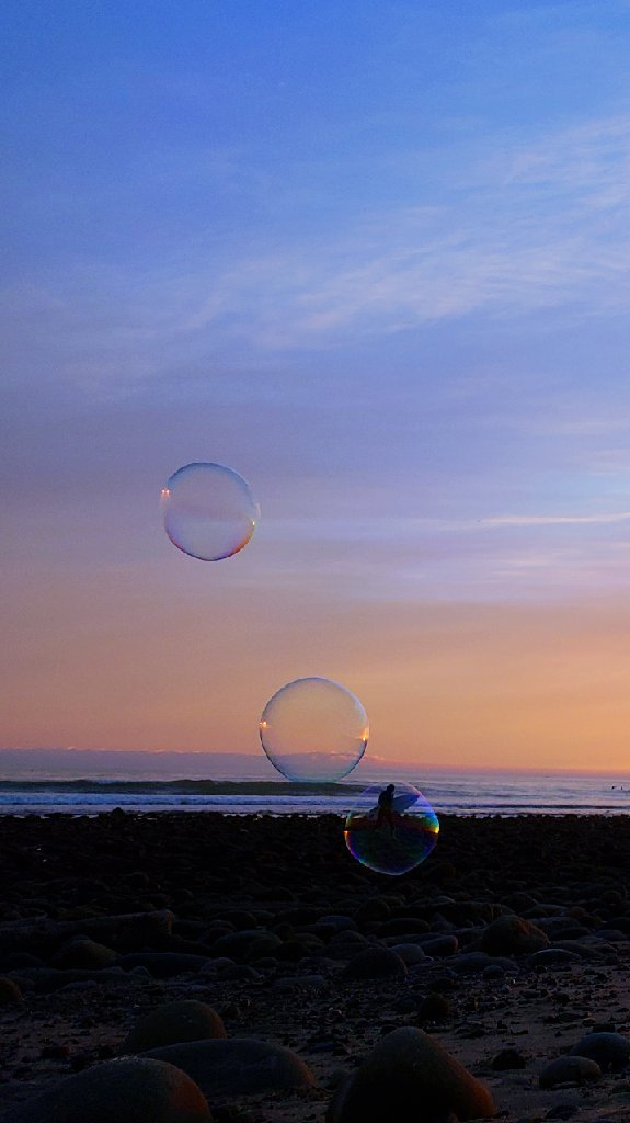 bubble frames surfer carrying surfboard. 2 more bubbles float above behind him. Blue and orange sky.