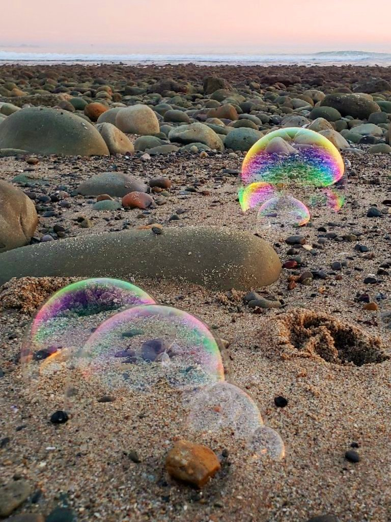 three colorful bubbles in foreground on sand, two colorful bubbles in background on rocks, ocean in background