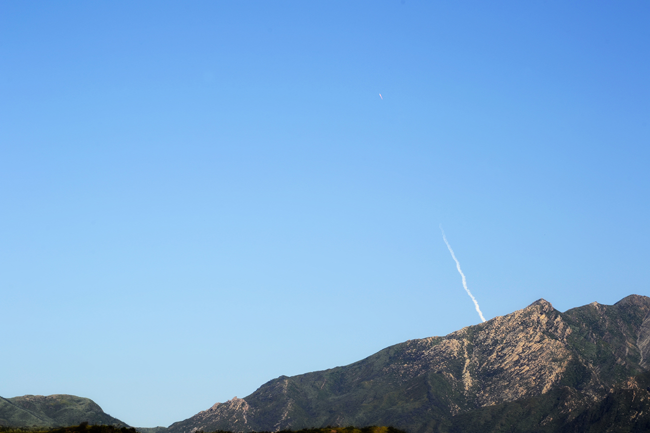 Rocket comes out over hill peaks, morning light, blue sky
