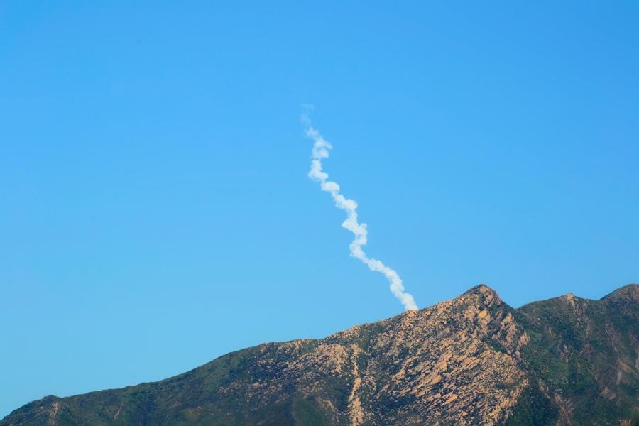 Jettison smoke swirls diagonally upward against blue sky, above hill peaks