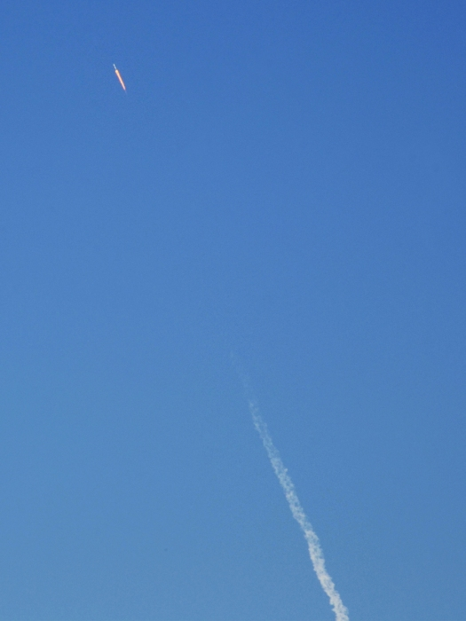 Stage 1 rocket and jettison smoke against blue sky, heading up and south