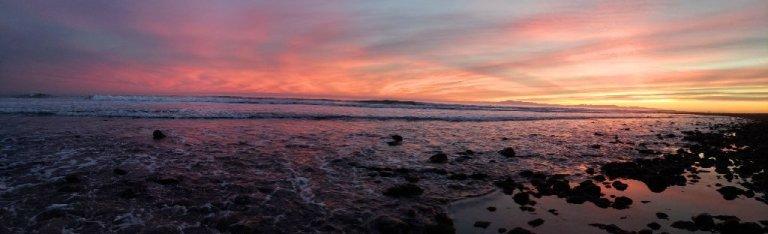 rocky shoreline, pink yelllow sky over long wave