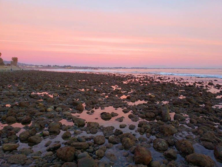 Ventura Pier under pink skies. Pink water between rocks on shore.