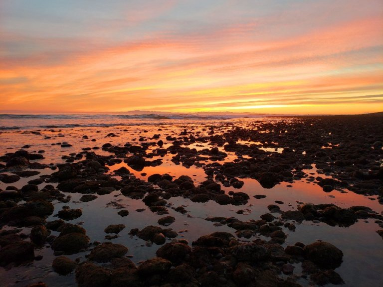 yellow, orange and pink sunset, reflecting off of tide waters beteween rocks
