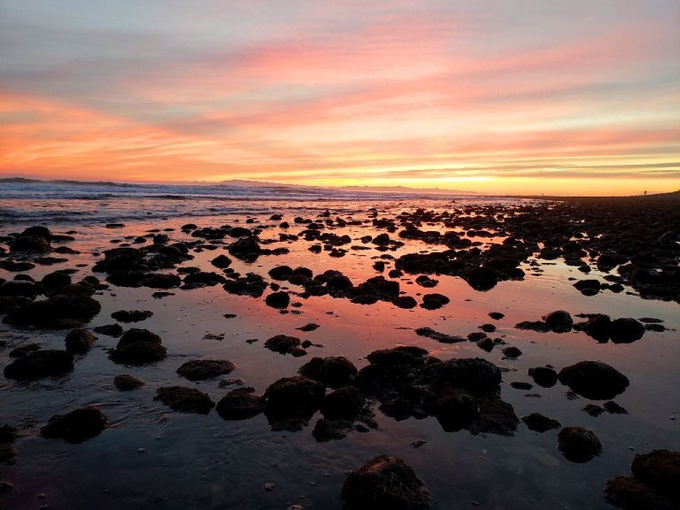 pink, yellow and orange sunset. Pink reflecting off of water between rocks on shore.