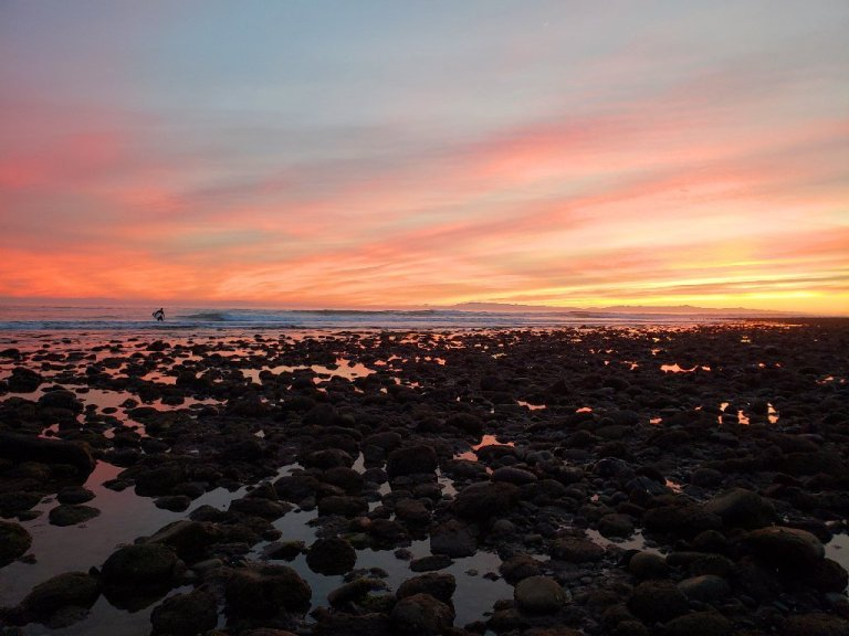 rocky shoreline, surfer walking away from waves, pink and yellow sunset