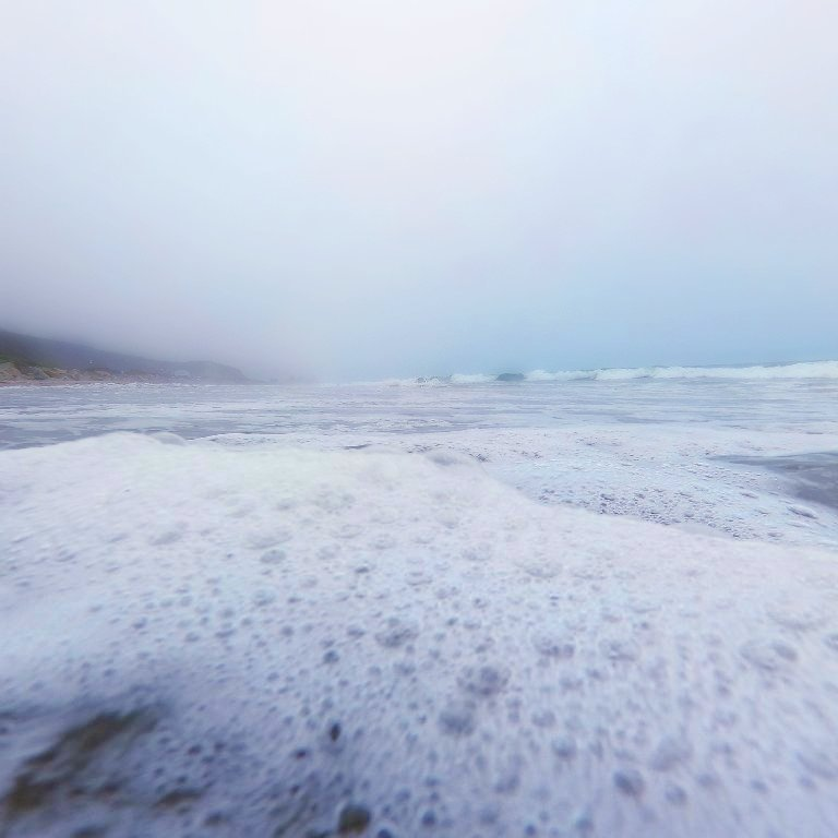 cloudy horizon, seafoam in foreground, waves and hills in background