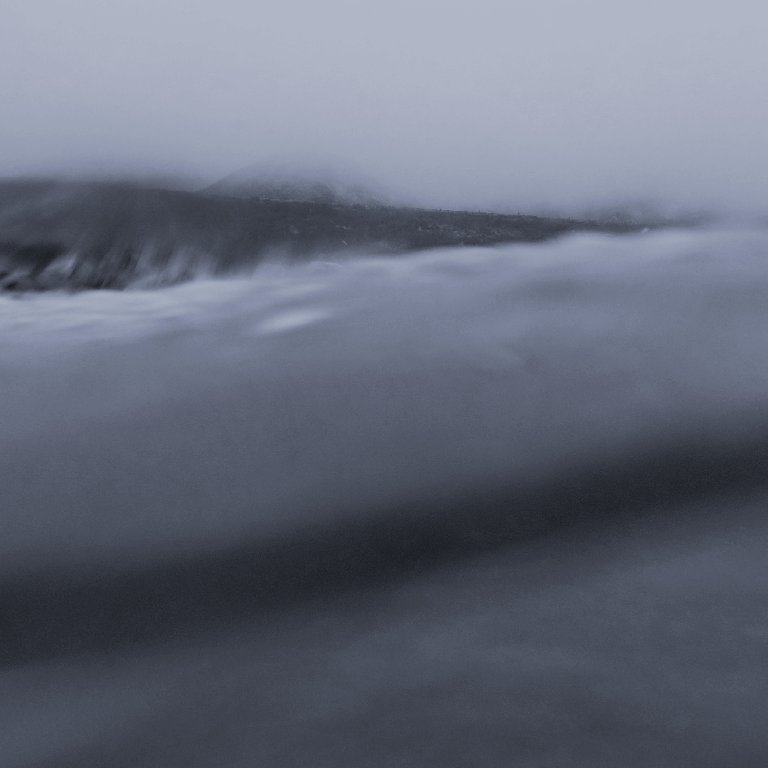 view of foggy coastline as seen behind a wave from the ocean, grayscale, soft blur