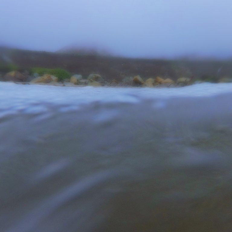 view of foggy coastline as seen from the ocean, rocky shore and hill in background, soft blur