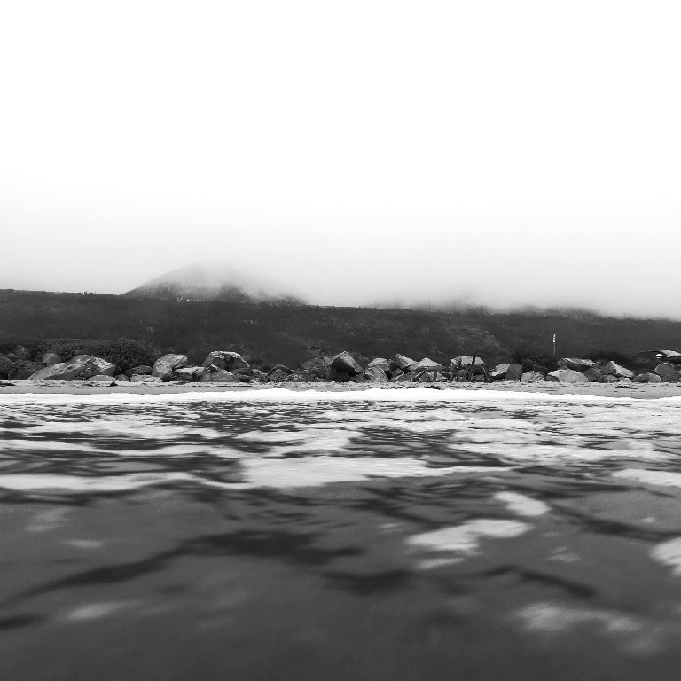 view of foggy coastline as seen from the ocean, grayscale, rocky shore and hill in background