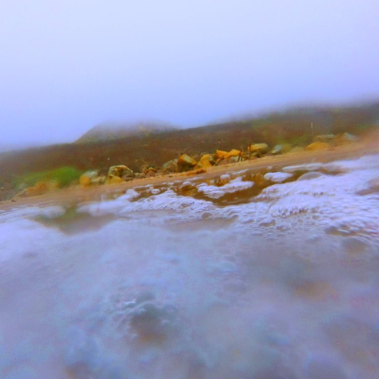 view of foggy coastline as seen from bubbly ocean, rocky shore and hill in background