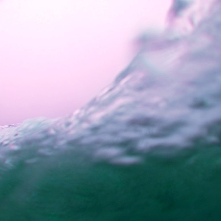 view of ocean wave as seen from behind another turquoise wave, pink surreal sky