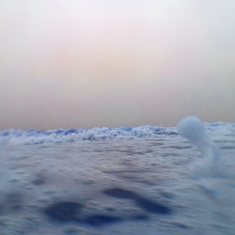 gray sky with hints of pinkish orange, hyperblue waves and seafoam splashing in foreground